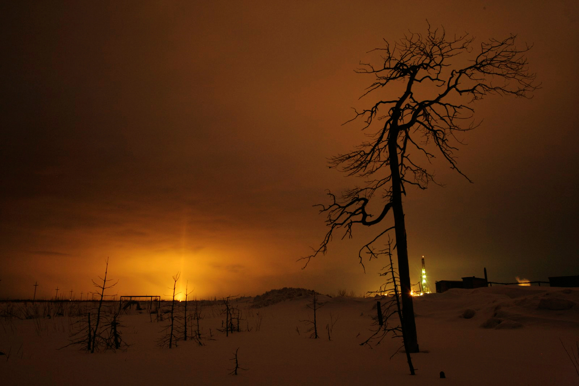 Gas flares and rig lights sear the night sky. Russia is now the world's top producer of crude oil.  Savuiskoye oil field, Russia