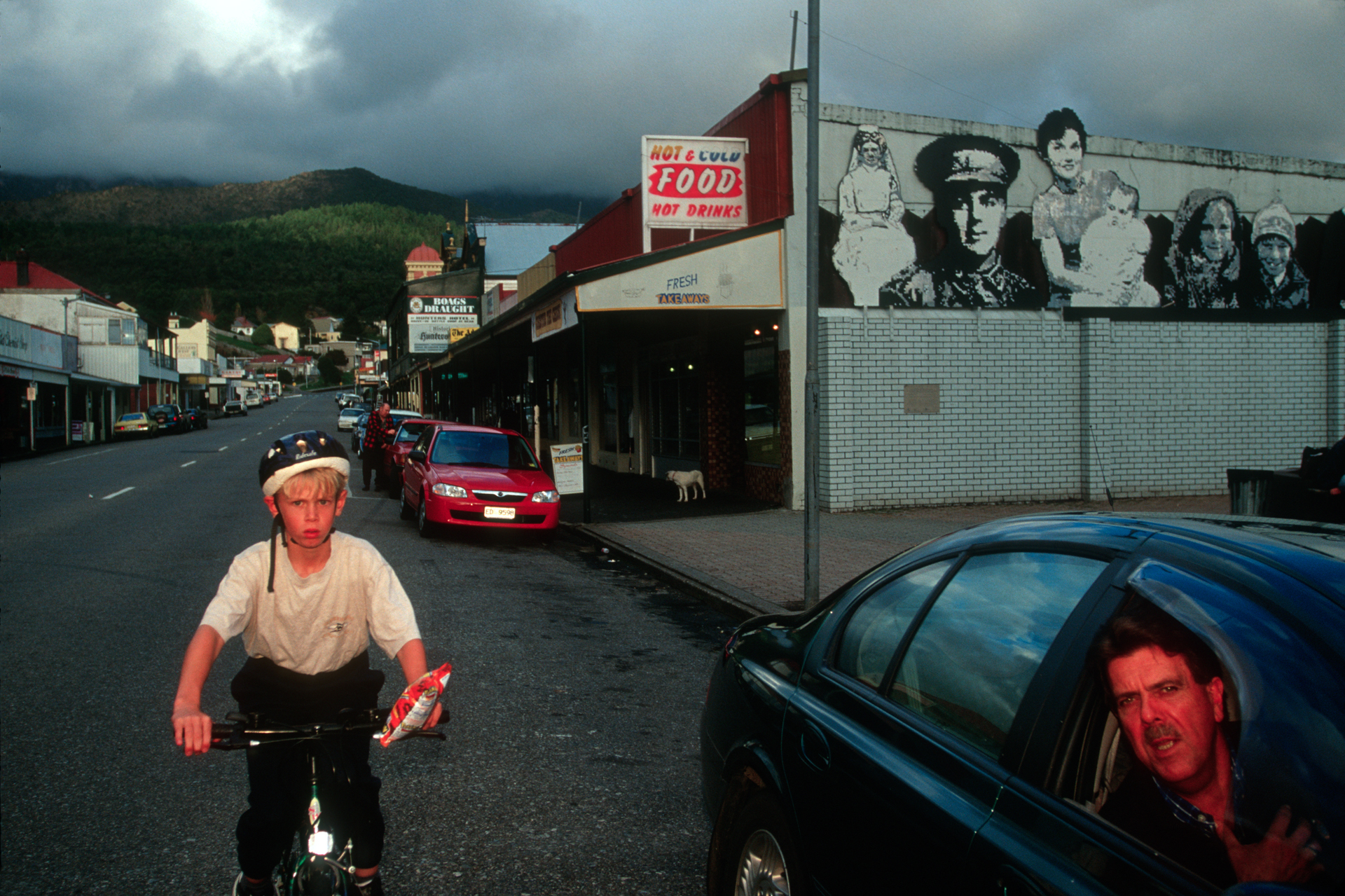 A child on bike and a few parked cars on Main Street are typical for traffic in Queenstown.  Queenstown