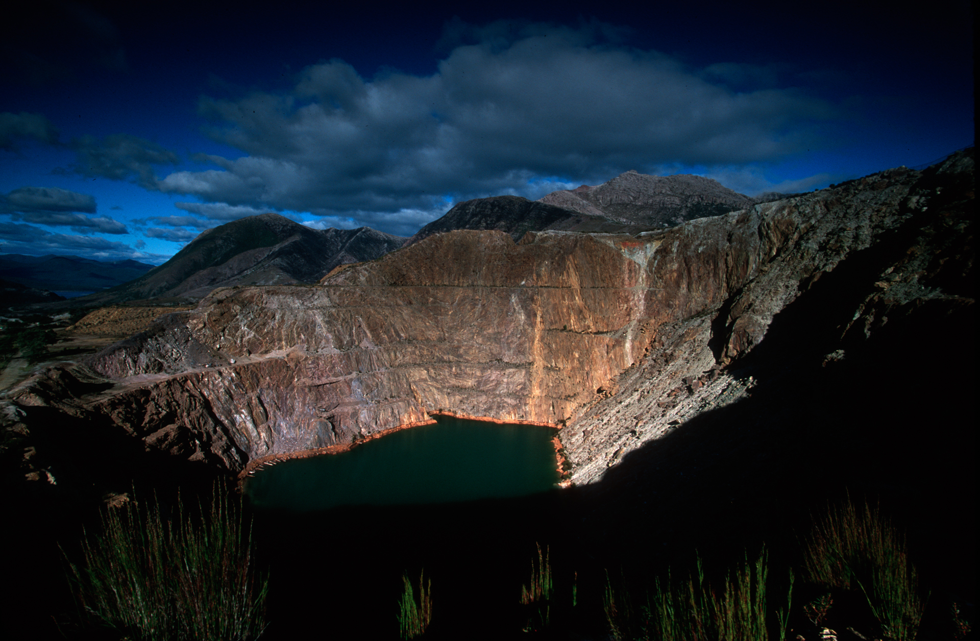 """View of the """"Iron Blow"""", a deserted and flooded open-cut mine near Queenstown.  Queenstown"""