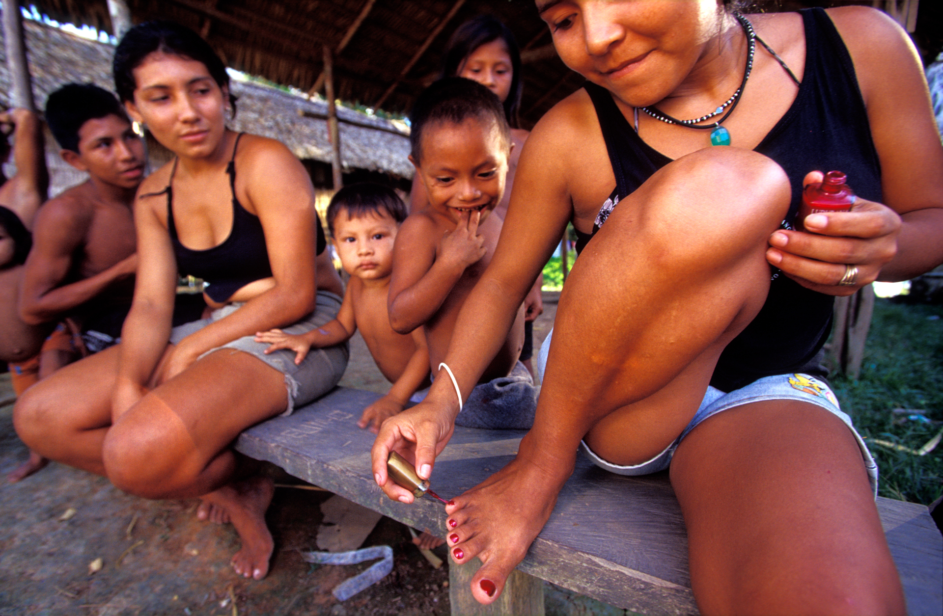 A young Indian girl proudly paints her toenails in public. Avon products are among the few luxury items accessible in the smaller communities around the Rio Cunuma.  Kwata, Brazil