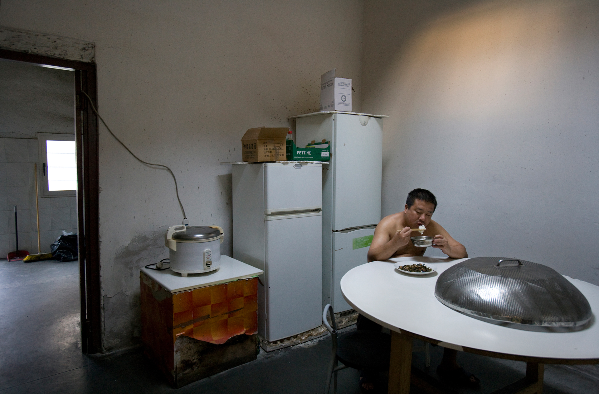 A Chinese laborer takes a break from the textile factory floor for a brief meal before returning to work.
