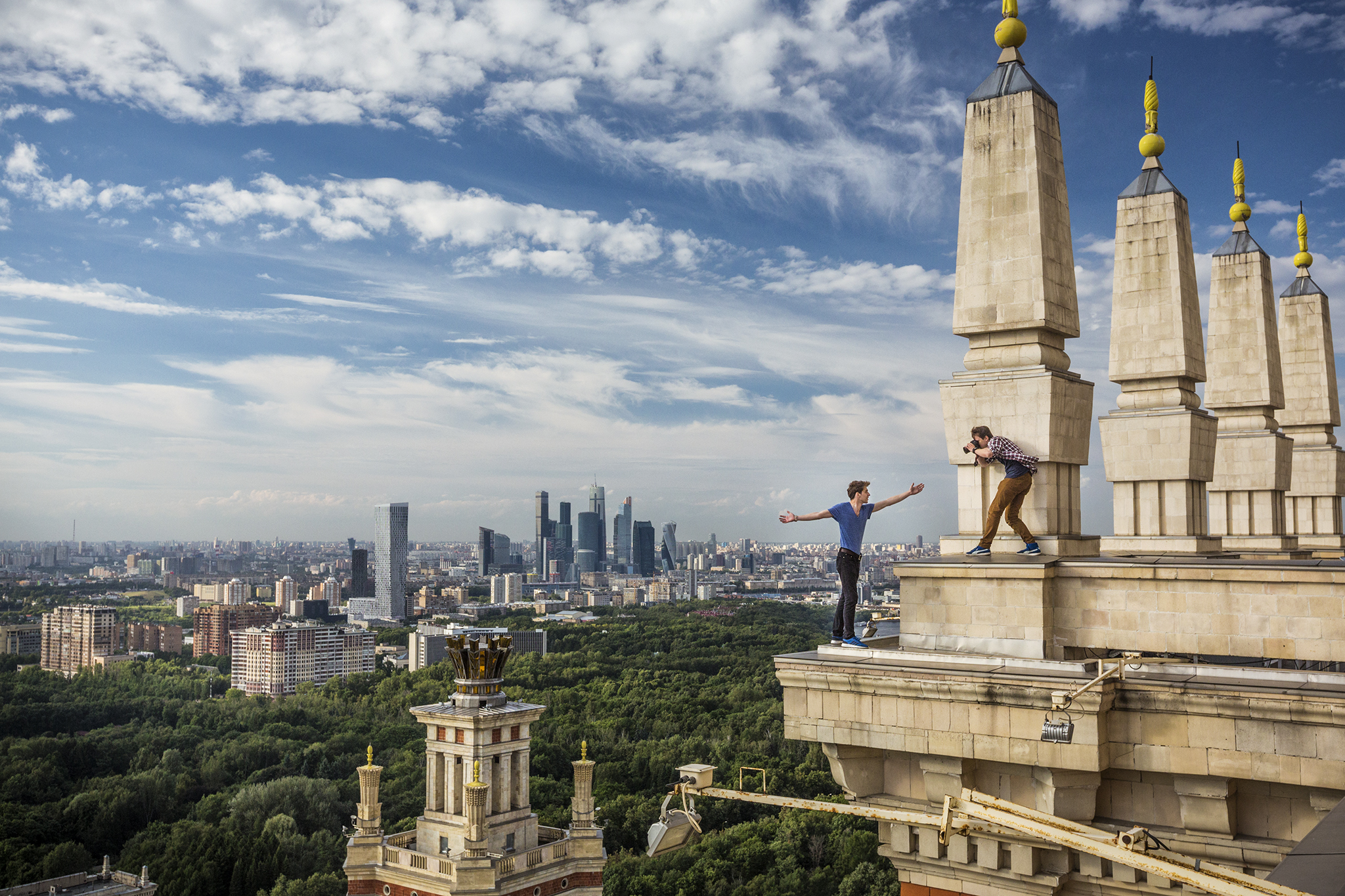 "Kirill Vselensky perches on a cornice in Moscow as Dima Balashov takes his photograph to celebrate their adventures on Instagram. The 24-year-olds are prominent members of the city's death-defying ""roofer"" or skywalker community. They scale Russia's highest buildings, without safety gear, often entering illegally and using whatever tools necessary to reach their destinations.  Moscow, Russia"