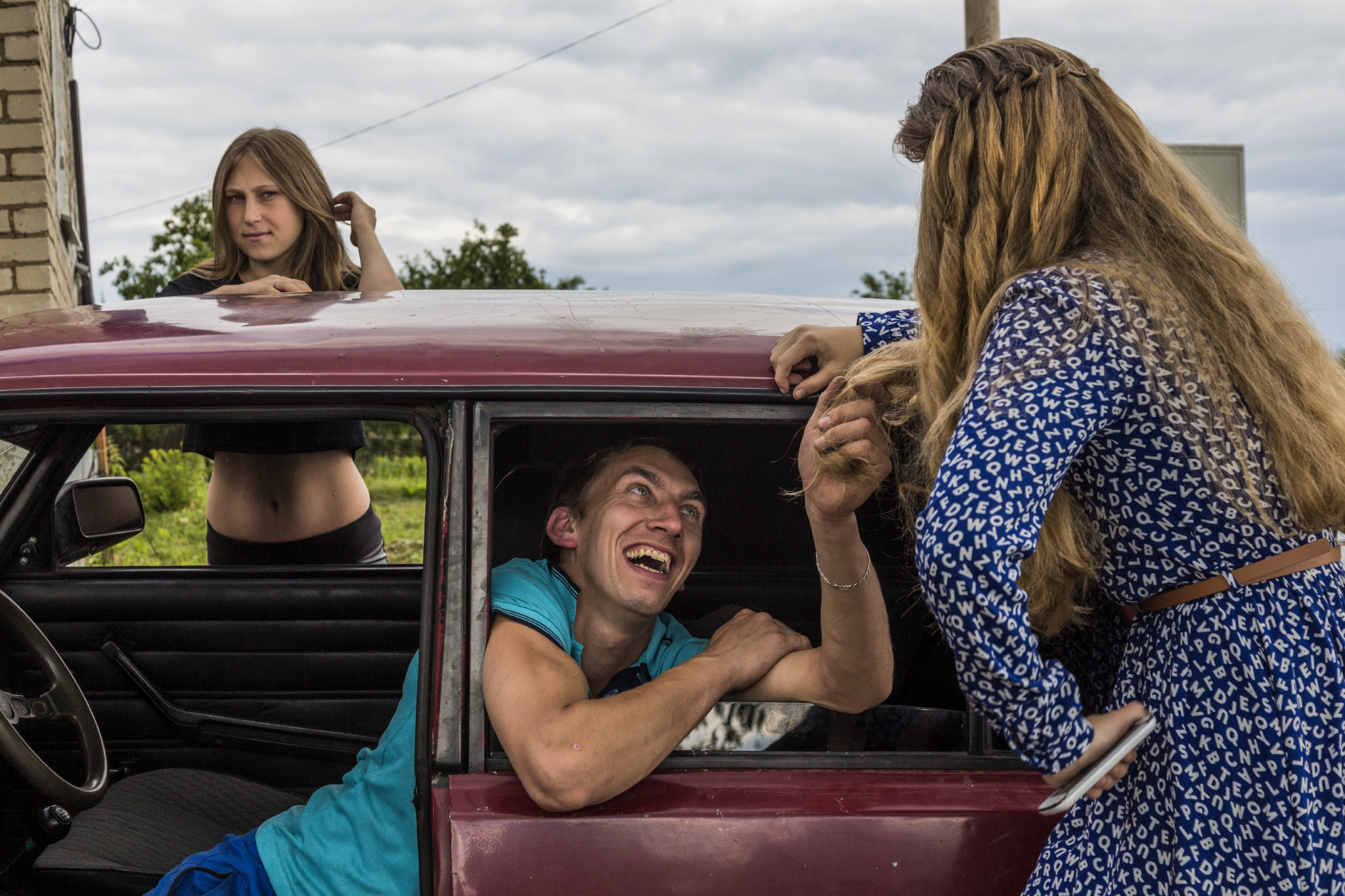 "Before the ""Day of the Village"" celebration, young people in Nikolskoyedo do what young people do everywhere when entertainment is sparse: hang out and flirt. Until recent downturn, the century's oil-fueled economy expanded rapidly, and Russia's young flocked to its cities to seek higher paying jobs.   Nikolskoyedo, Russia"