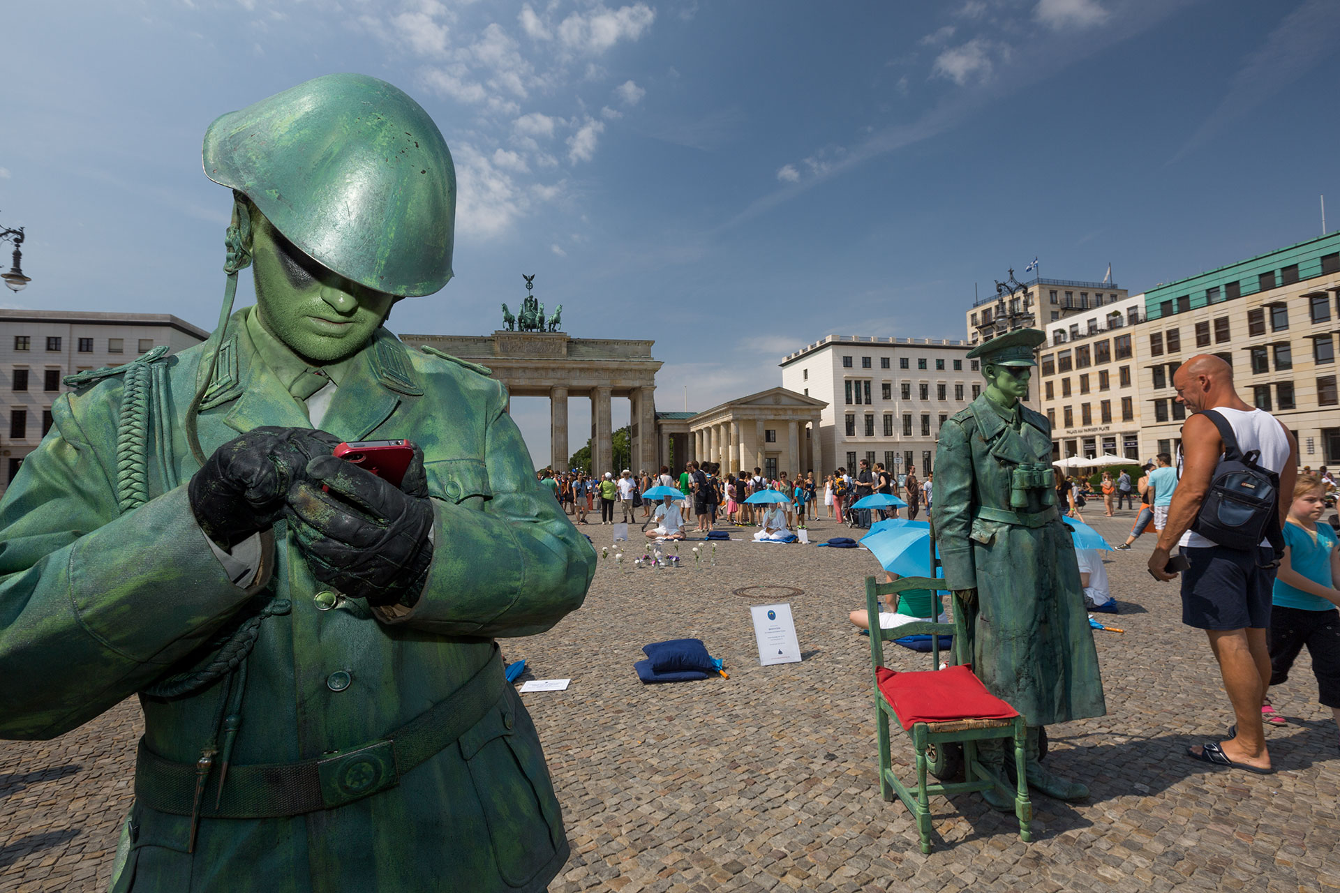 A Slovakian street artist poses as an East German border guard in front of the Brandenburg Gate.  Berlin, Germany.