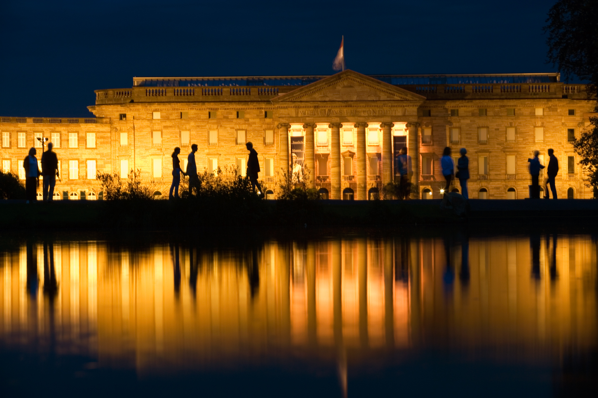 As evening descends, the lights of the Schloss Wilhelmshöhe are reflected in a small park lake.   Kassel, Germany
