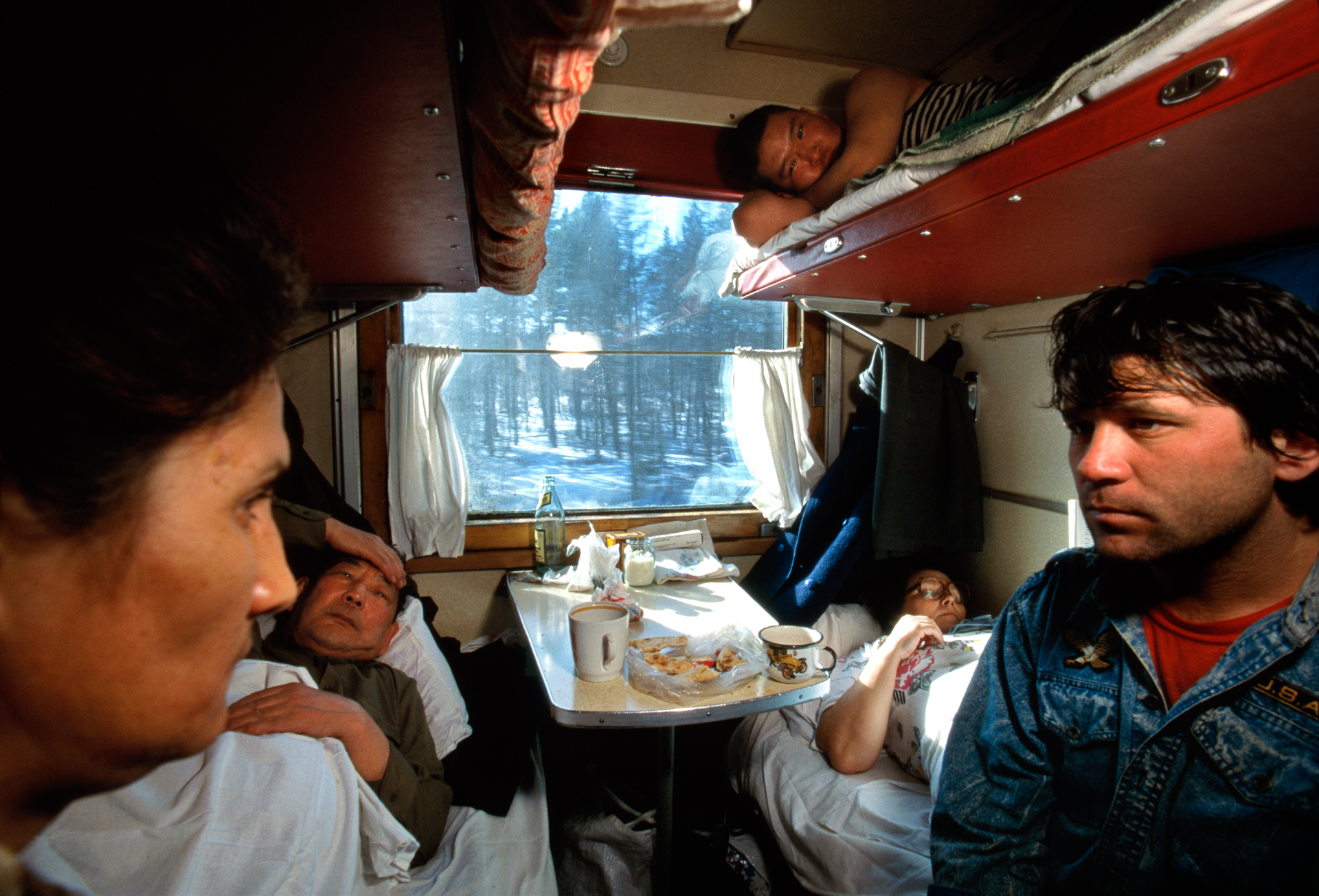 "Crowding, boredom, and vodka mixed with age-old ethnic hostilities charge this communal car with silent tension. Nearing the Amur River some 4,000 miles and six time zones from Moscow, ""train-lagged"" passengers grow bleary-eyed and irritable.  Near the Amur River, Russia"