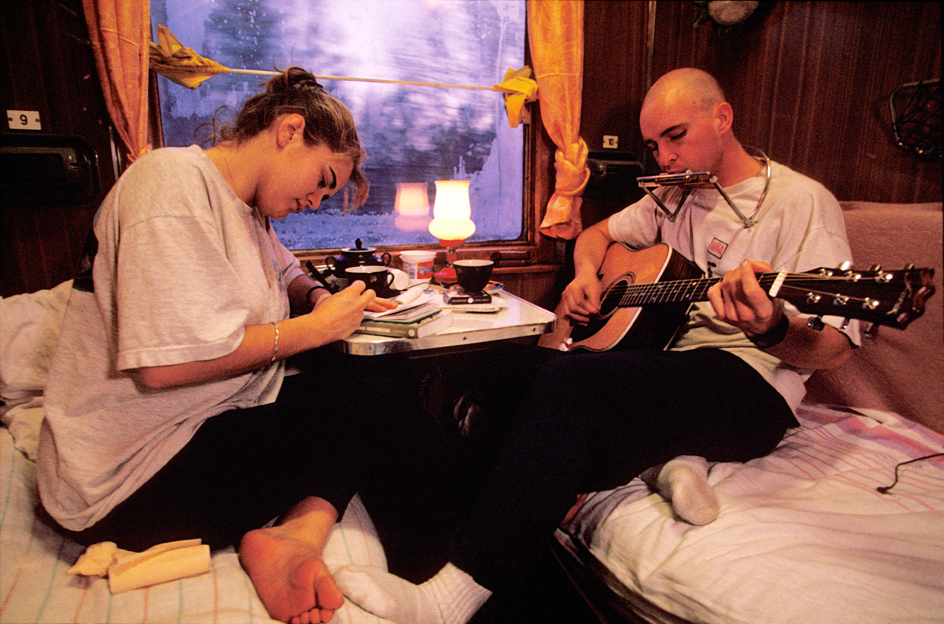Anna and Peter, 2 young world travelers from Western Australia, spend their evening writing letters and playing guitar from their two-person compartment on the Trans-Siberian Railroad.  Perm, Russia
