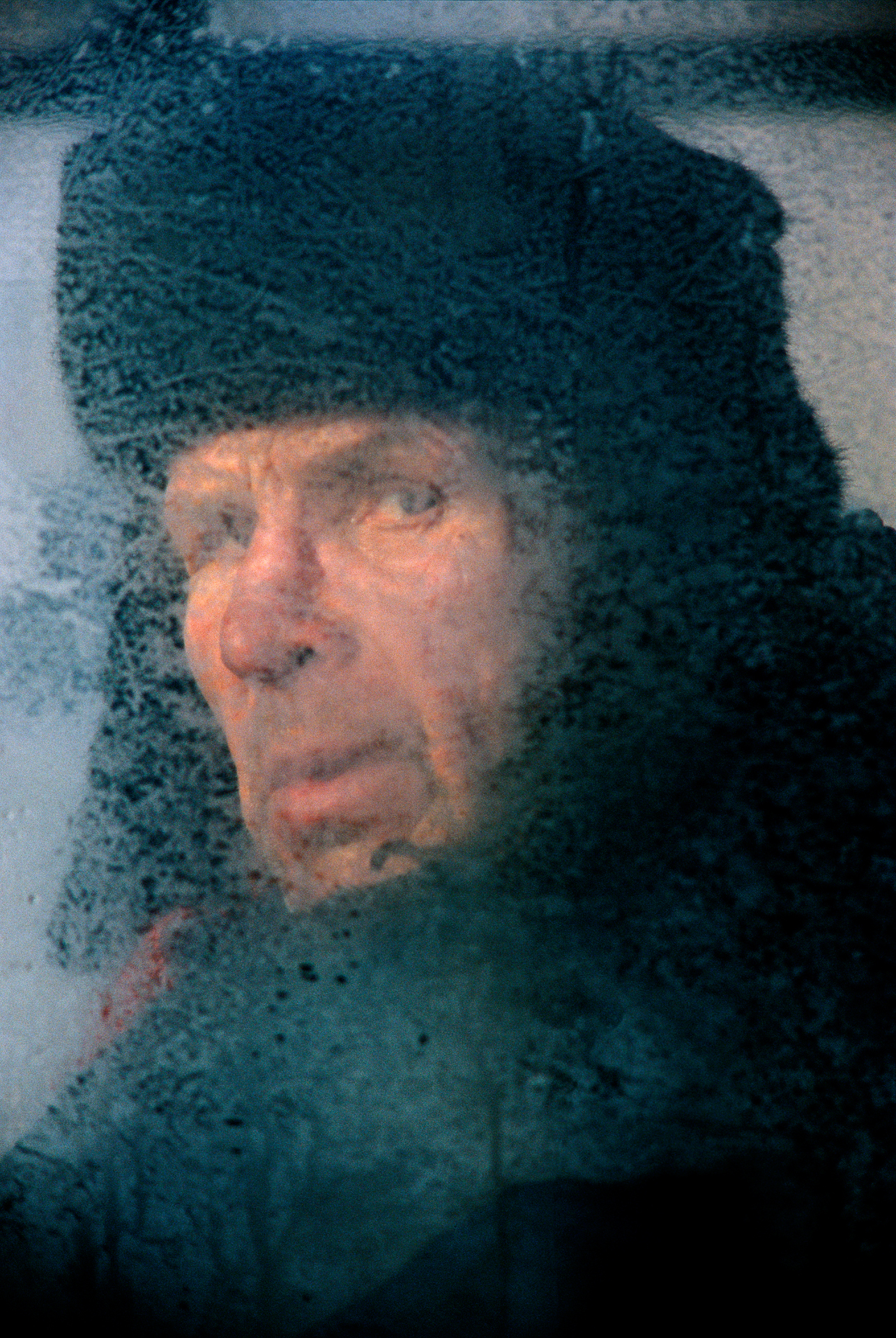 In south-central Siberia, biting cold frosts the windows of an electrichka, a local electric train, where a passenger sports the classic Russian defense against winter – a fur shapka.  Krasnoyarsk, Russia