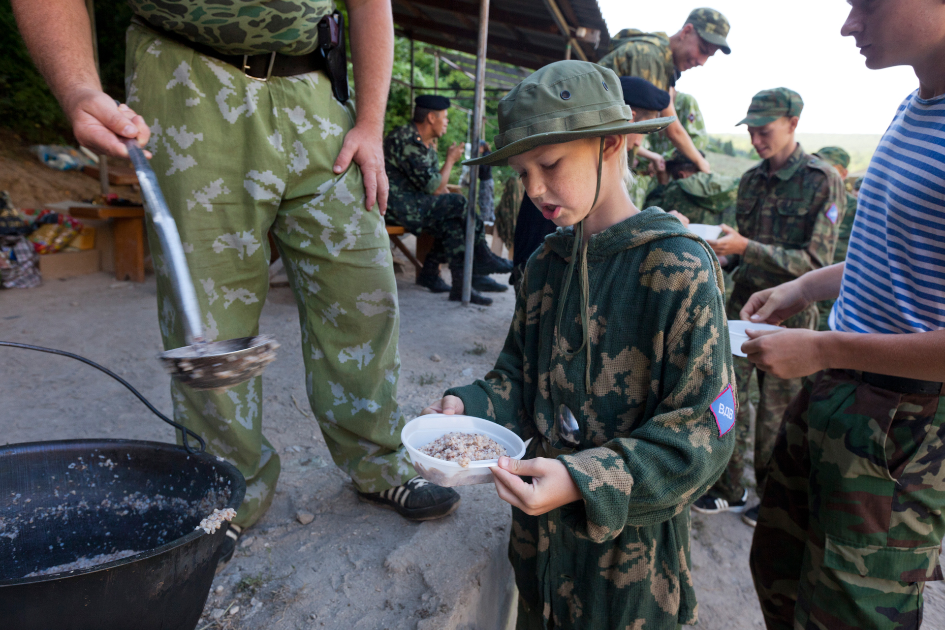 A young attendee frowns over the bland meal offered at the Cossack camp.  Eski-Kermen Region, Crimea
