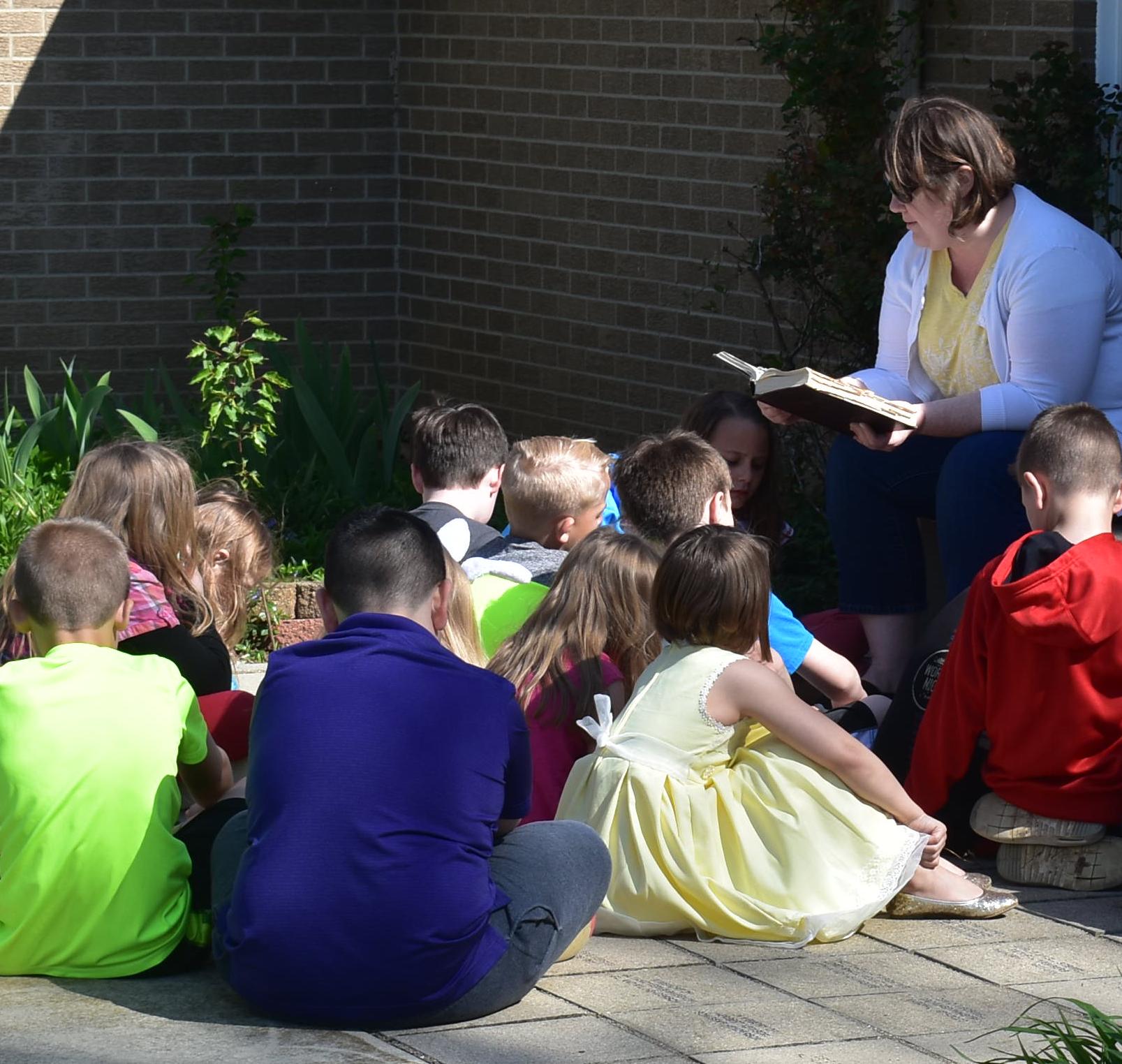 Mrs. Bond reading to her First Grade class in the prayer garden.