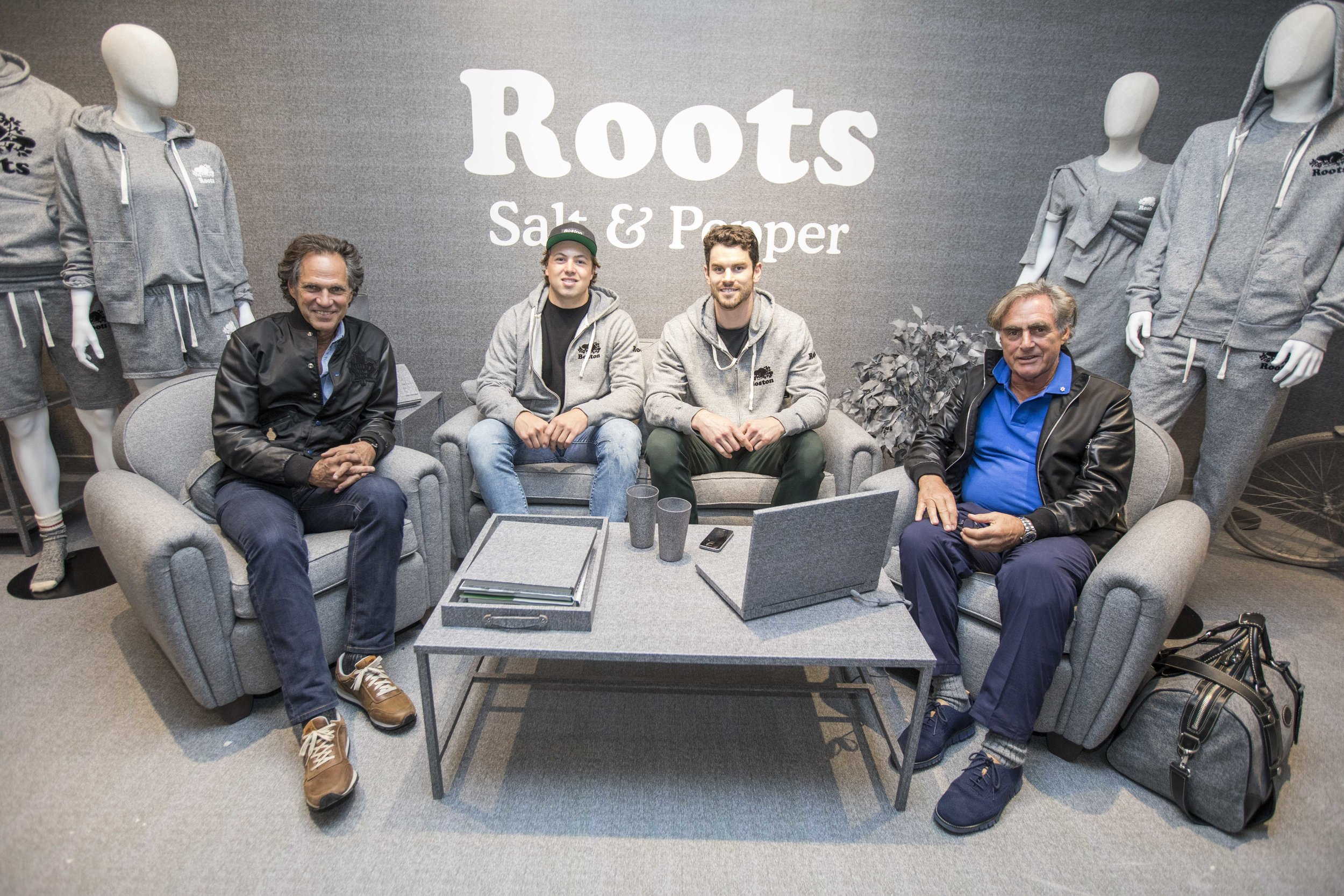 Roots Co-Founders, Don Green (far left) and Michael Budman (far right), with Boston Bruins players Charlie McAvoy and Adam McQuaid.