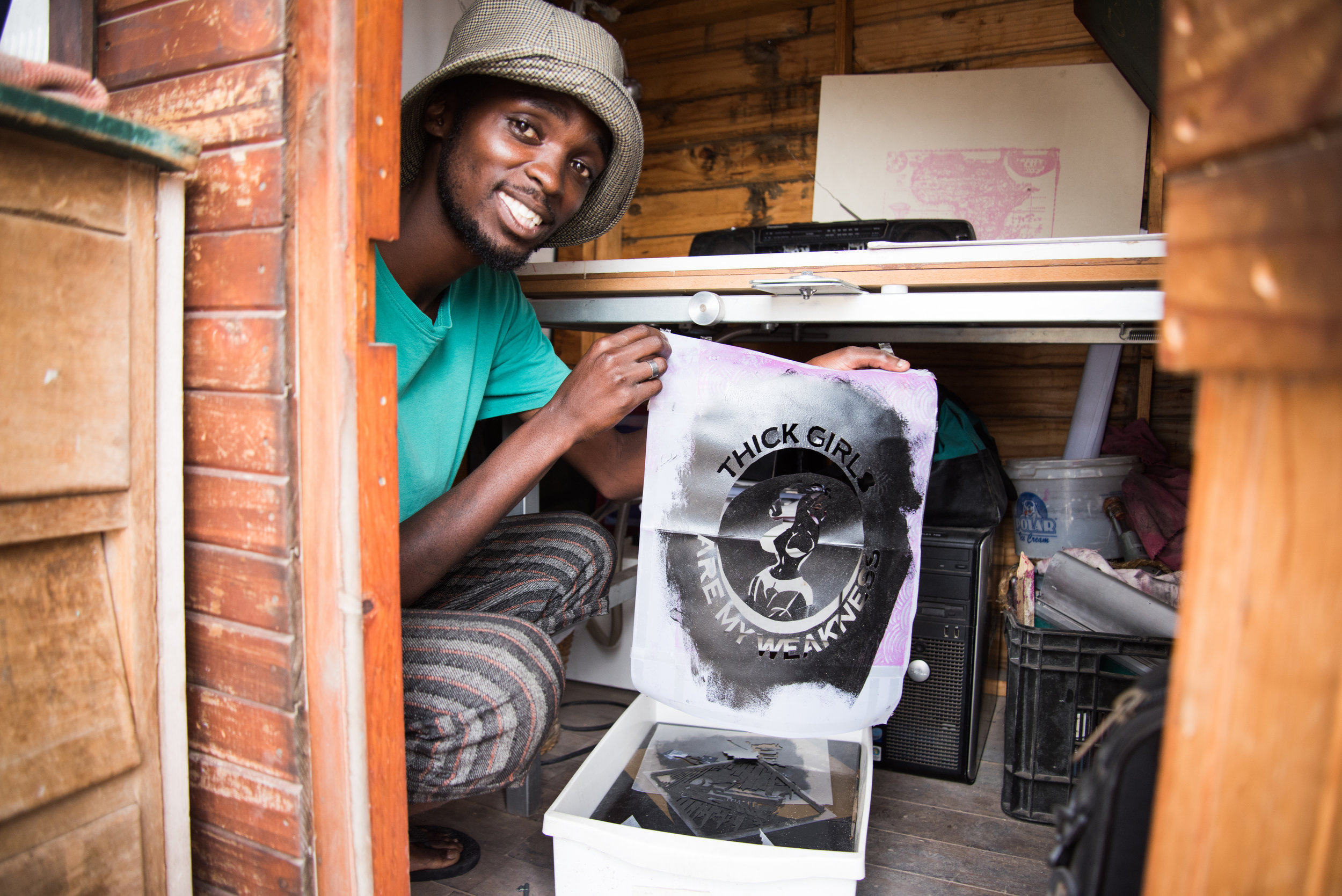 """Vumazonke holds up a t-shirt stencil he made claiming that """"thick girls are my weakness."""""""