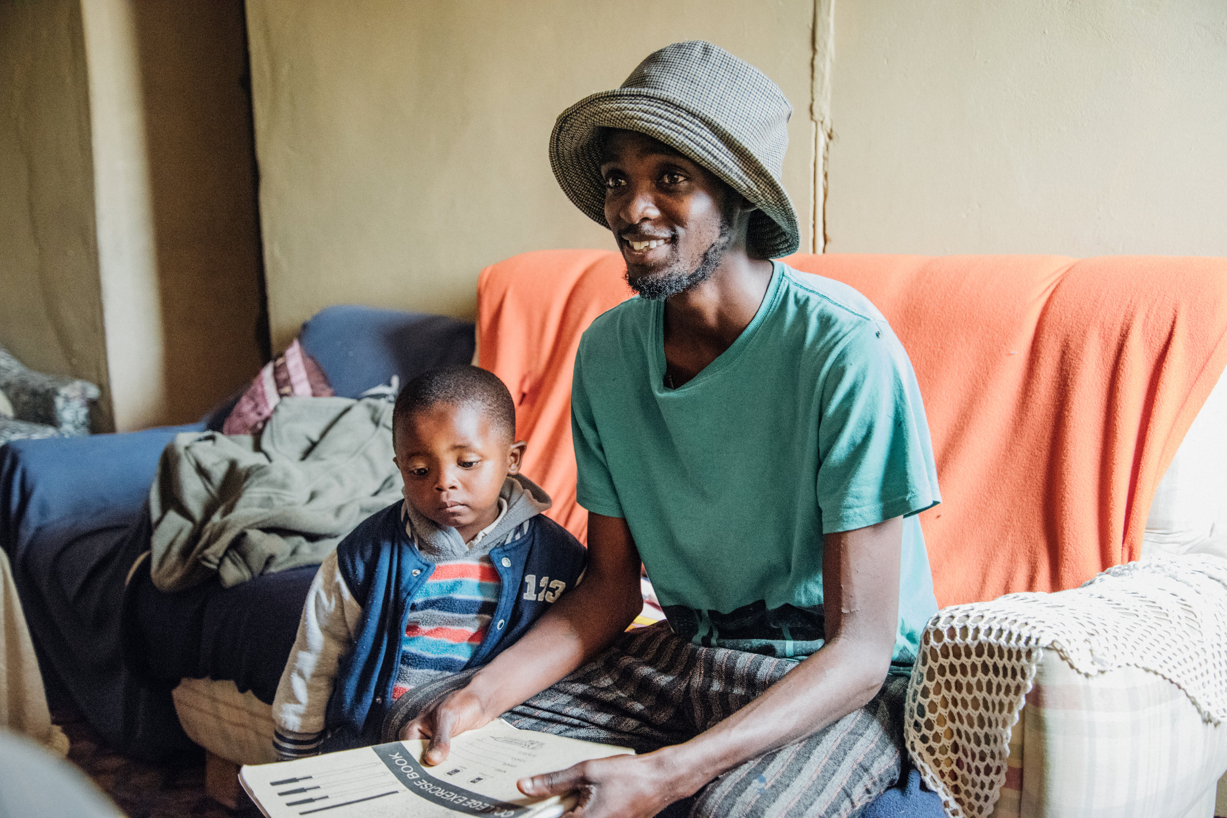 Vumazonke explaining his artwork with his son at his side.