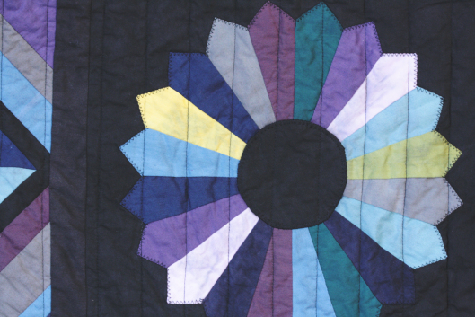dresden-plate-on-black-and-color-quilt.jpg