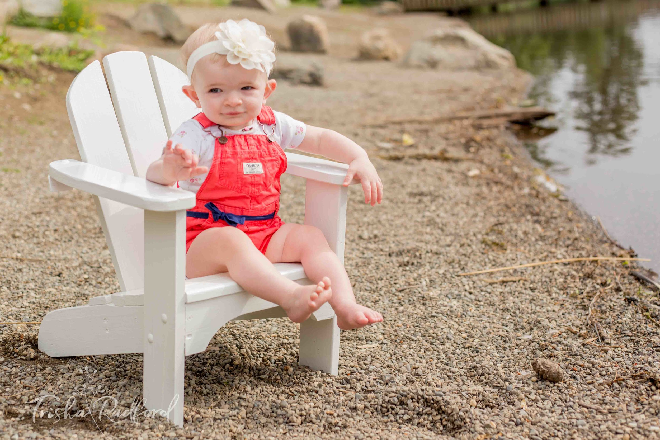Toddler girl sitting on chair at the beach