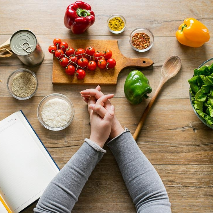 woman-leaning-on-table-with-various-ingredients-and-a-diet-planning-book_1200x1200.jpg