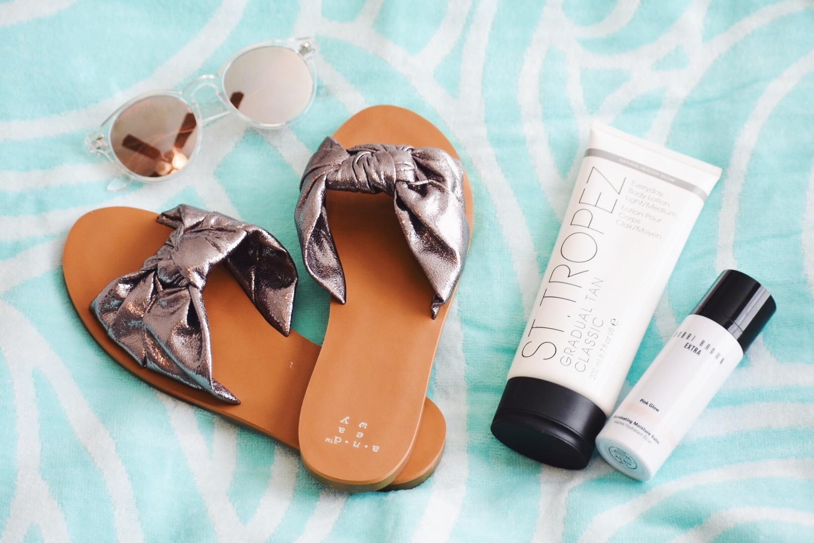 The last few items that are absolutely essential for spring are: more sandals {duh}, sunglasses, a fun beach towel, and lotion to help you glow this season!  Target is a great place to stock up on sandals at a really reasonable price. They also have an array of sunglasses and beach towels to choose from to match anyone's budget!  The next two items are perfect for people who don't like spray tans/tanning beds, but still want to glow this spring. I am a very pale person and I'm proud of it! I love my skin tone, but coming out of winter I always look more than just pale-try transparent? I started using St. Tropez gradual tan lotion to help me get a nice glow going for my trip. So far I'm not orange nor do I have streaks! It's definitely a great brand for self tanning that is subtle, doesn't smell and actually works!  Bobbi Brown is who I use for makeup and skincare products. I have super sensitive skin and this brand has yet to break me out! I use their Pink Glow Illuminating Moisturizer on top of my regular moisturizer to add a bit of a glow to my face, hands, shoulders, and chest area! You don't need a lot because a little goes a long way with this product. For people who don't like to tan these two products are perfect to help your skin look luminous this spring!