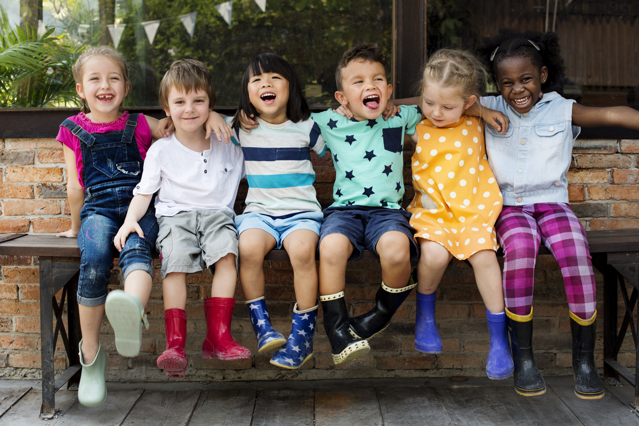 Kindergarten-kids-friends-arm-around-sitting-smiling-685864090_1256x838.jpeg