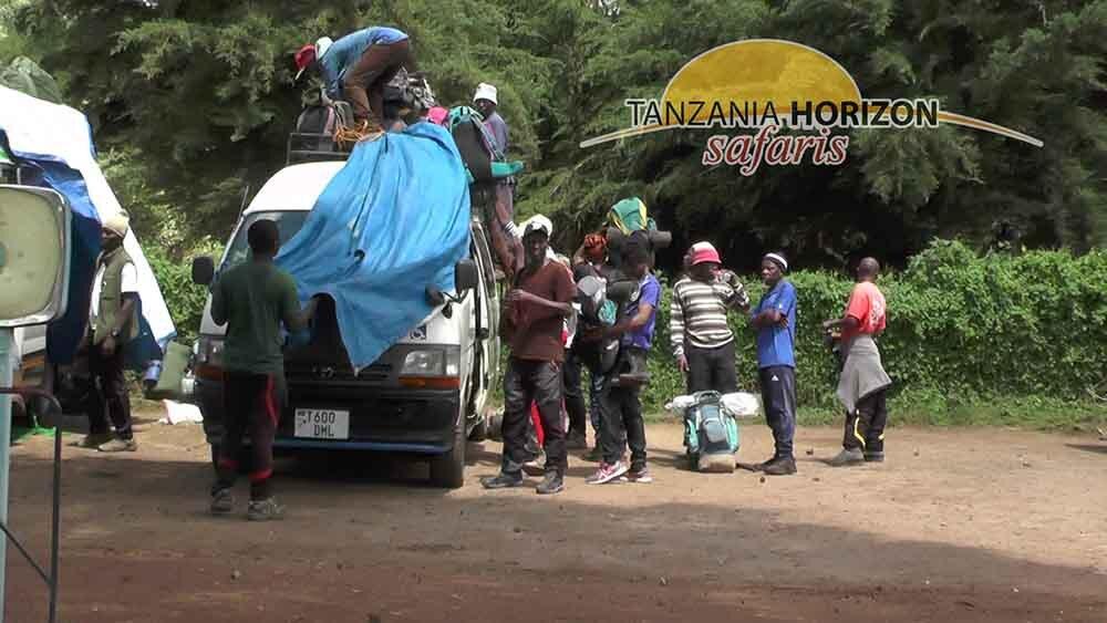 Porters UnLOADING ALL LUGGAGE BEFORE STARTING TO CLIMB KILIMANJARO / TANZANIA HORIZON SAFARIS