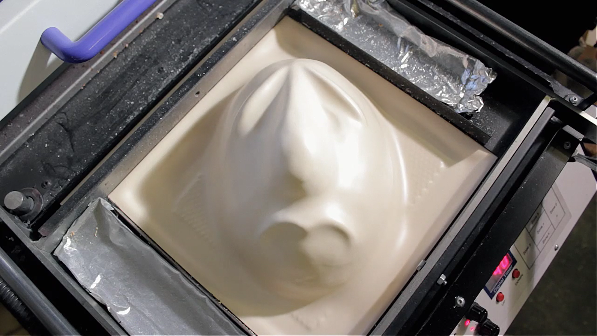 4) After about 20-30 seconds we see that the plastic has taken to the contours of the mould. We lift the plastic off the mould and let it cool for a moment.