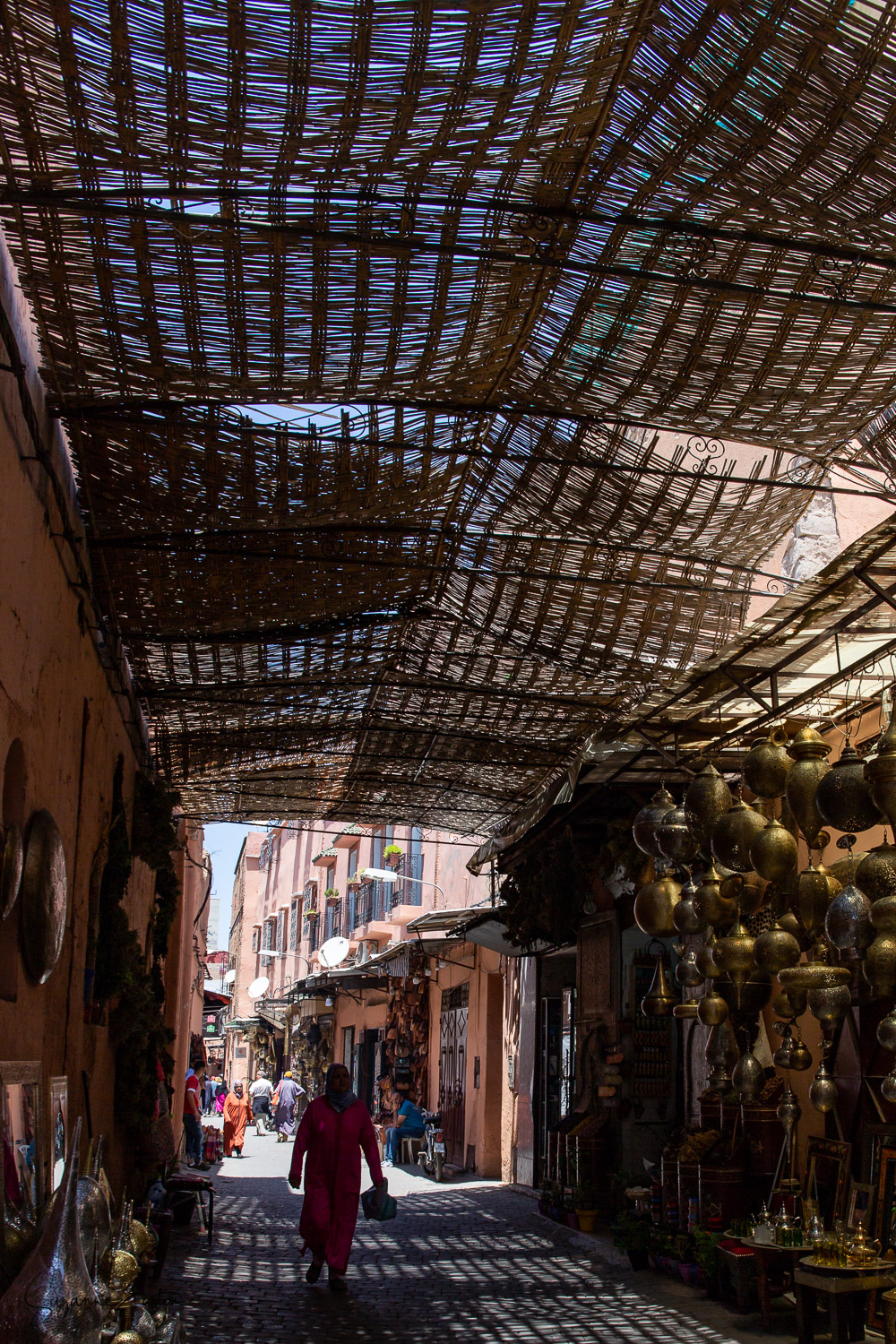 A non-descript alleyway with lanterns hanging from the rattan covers