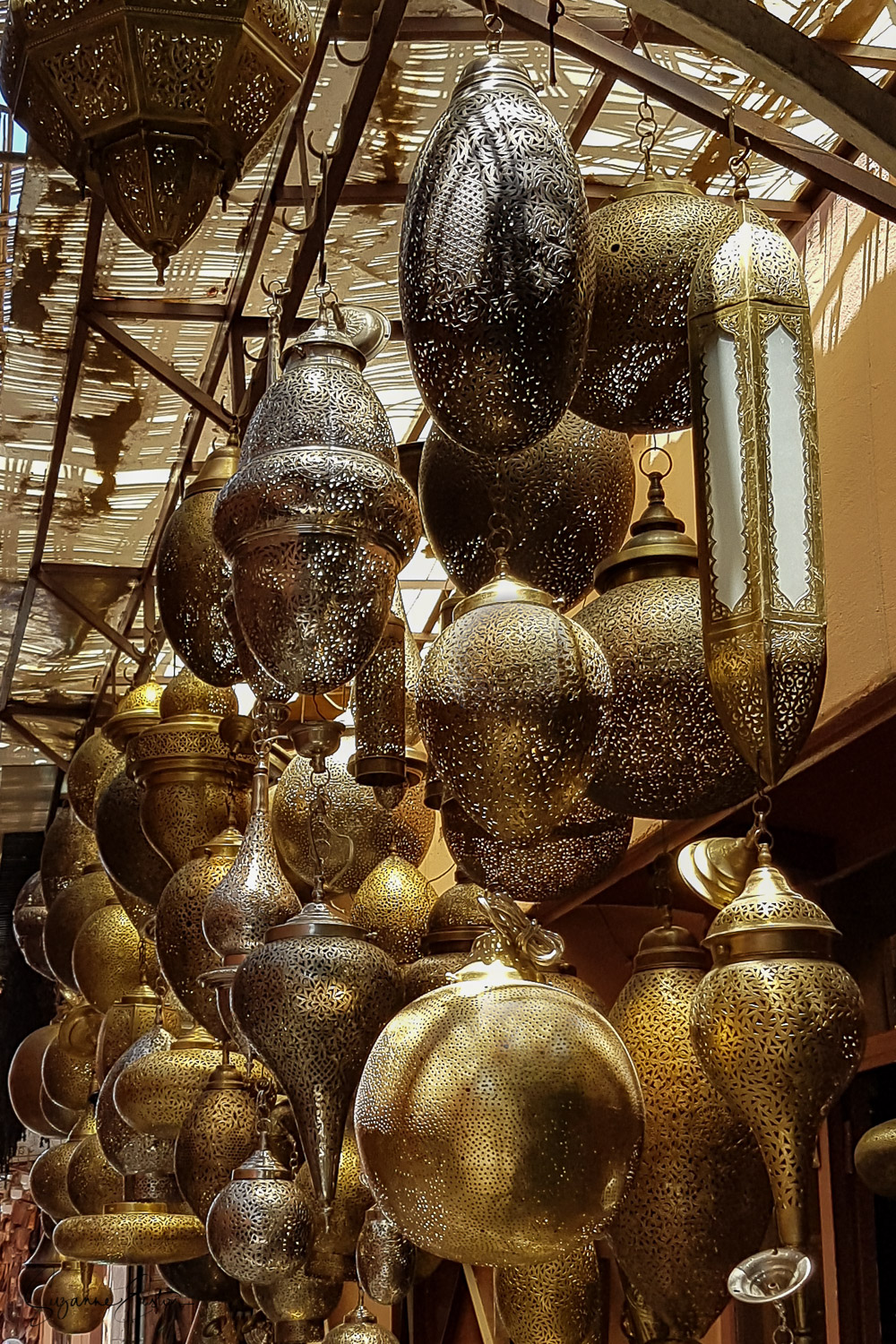 A shop full of copper lanterns in a Marrakech souk. Intricate patterns are carved into the golden copper to allow the light to escape and dance across walls and ceilings.