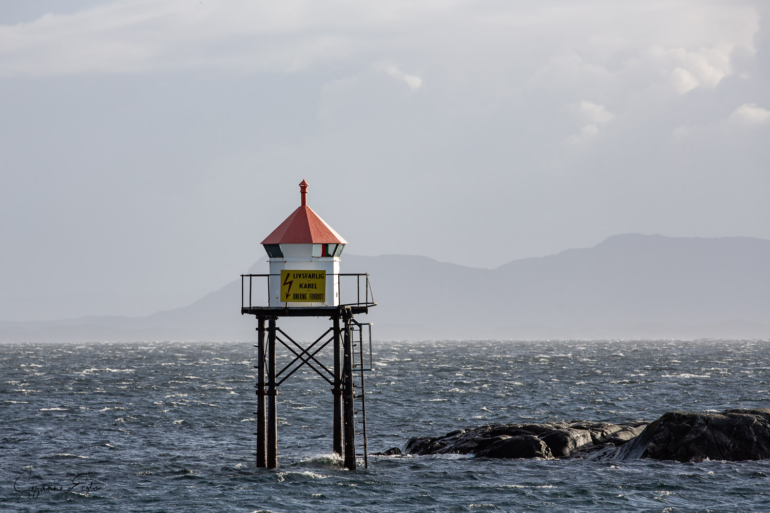 A light marker on the coast of Norway as a squall hits