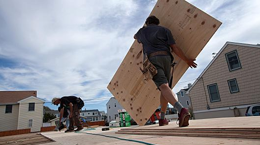Emile Wamsteker | Bloomberg | Getty Images  A construction worker carries a sheet of plywood as he and co-workers install the sub-floor of a home onto pilings.