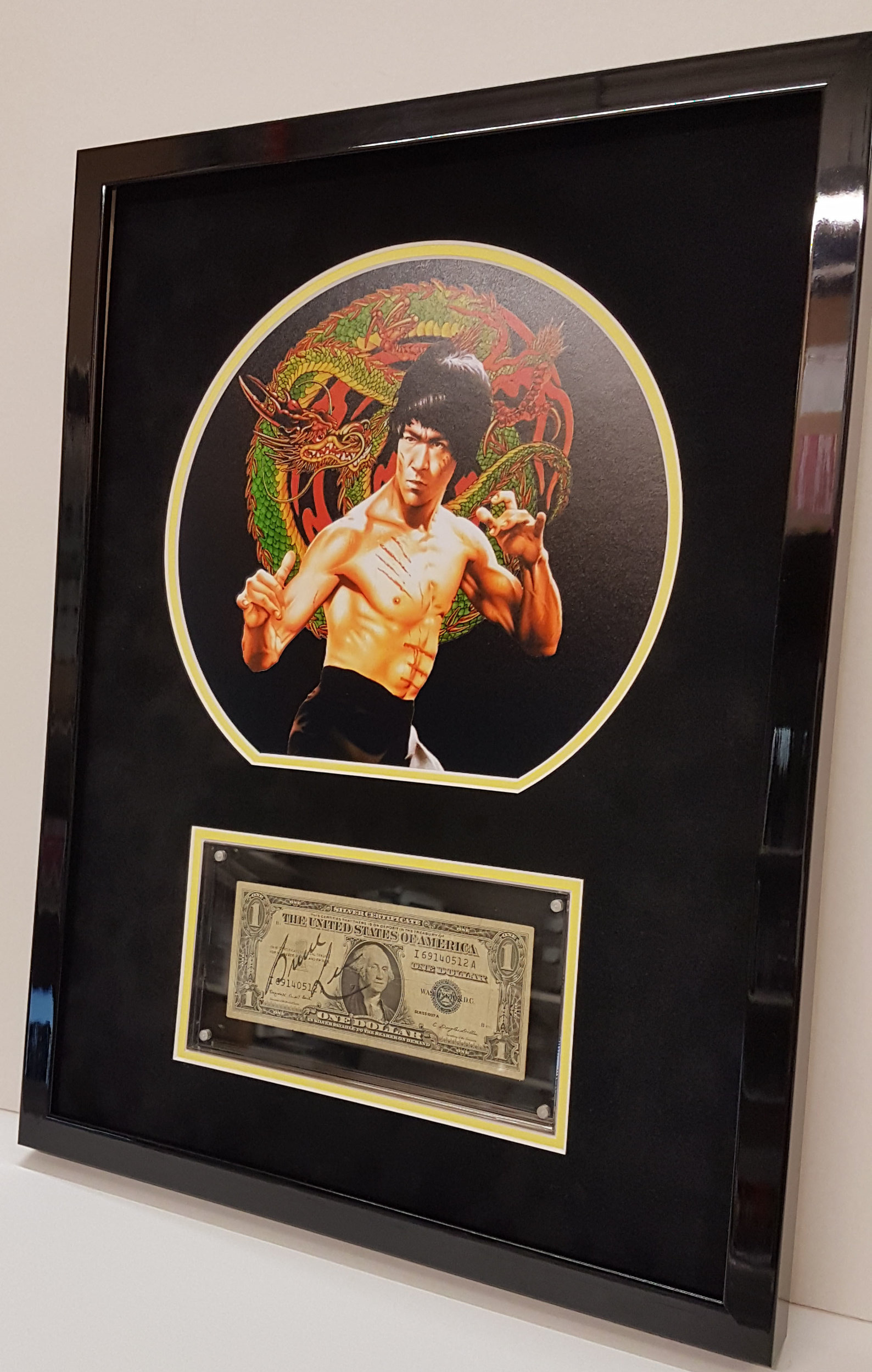 A Bruce Lee signed US dollar encased in its own perspex holder which had to be incorporated within the frame which meant we had to line the back and sides of the case in black without using adhesives. This then had to be held into place to stop it slipping. We framed this for Authentic Memorabilia.