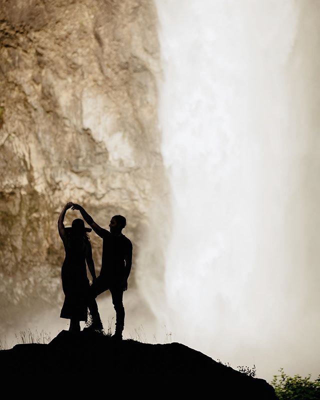 EPIC ALERT: I've had this idea for a silhouette on Snoqualmie falls as the sun sets and shades the foreground while lighting up the falls behind the couple. It WORKED 😍 __  This couple wanted a little bit of an adventure, but we also wanted to head into Seattle for an evening session. So we opted for Snoqualmie falls, which is not too far out, but still super cool! They brought a friend, and the 3 of them made it all the way out to my favorite area for some super cool photos. What an awesome evening 😍