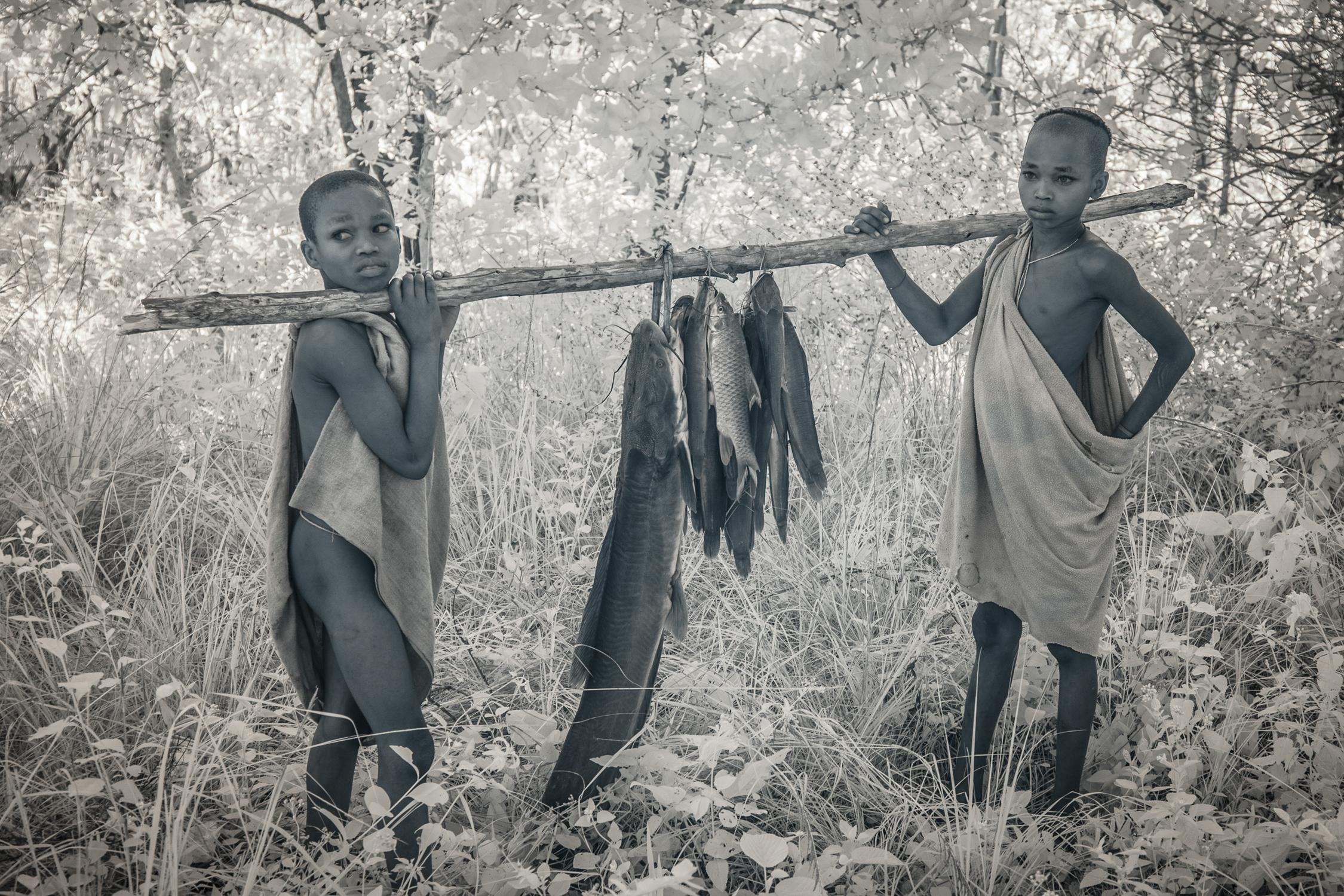Young Suri boys bring home freshly caught fish.