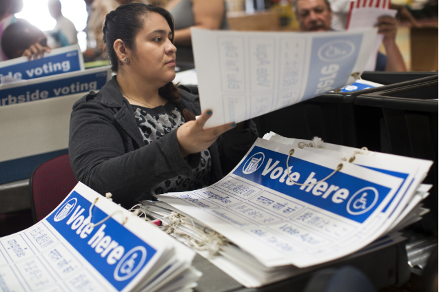 Joana Briones places signs into supply tubs on Thursday, Oct. 23, 2014 at Los Angeles County's Elections Operations Center in Santa Fe Springs. Photo by Maya Sugarman and courtesy of KPCC