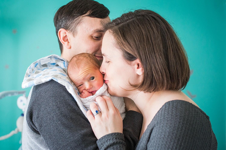 Parents kissing their newborn daughter.