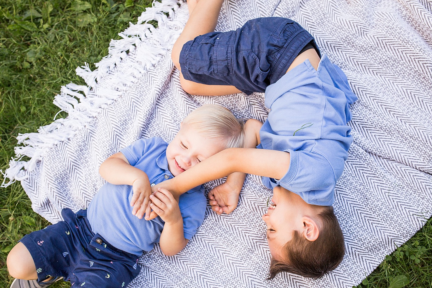 Photo of two little boys laying on a blanket and laughing.
