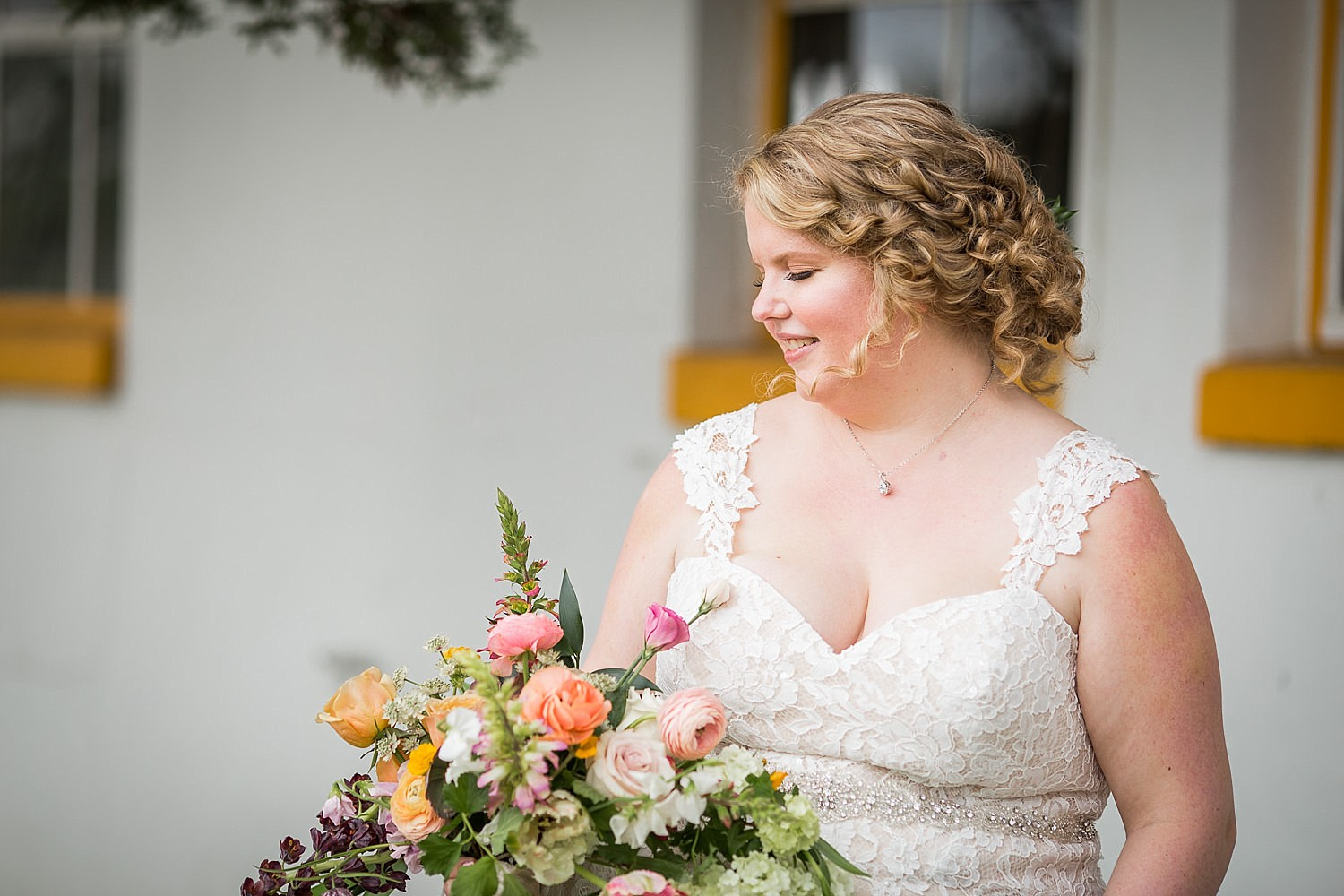 Photo of a bride with blonde hair and ringlets blowing in the wind as she looks down at her bouquet of flowers.