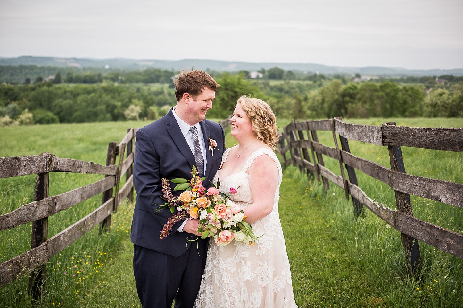 Photo of a bride and groom standing between a fence in a green field overlooking the Susquehanna River.