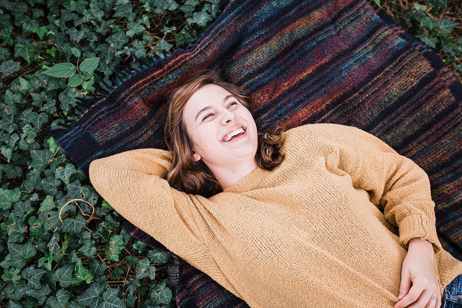 Lancaster senior session photo of a young girl in a yellow sweater and jeans lying on a striped blanket in a bed of ivy.