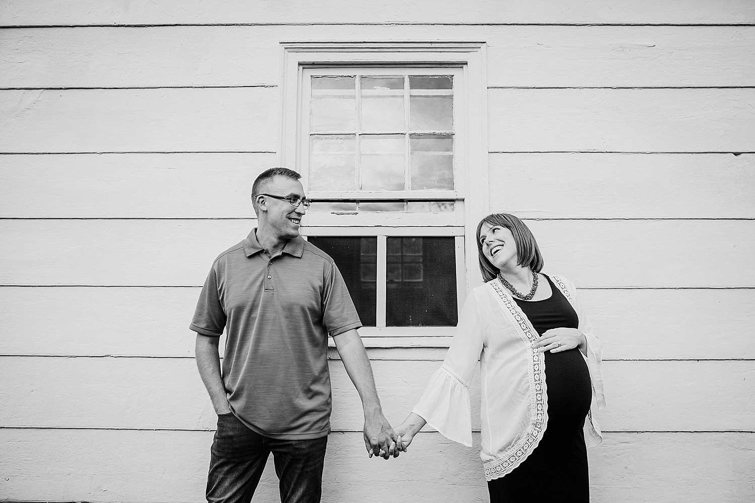 Black and white photo of a pregnant woman and her husband holding hands.