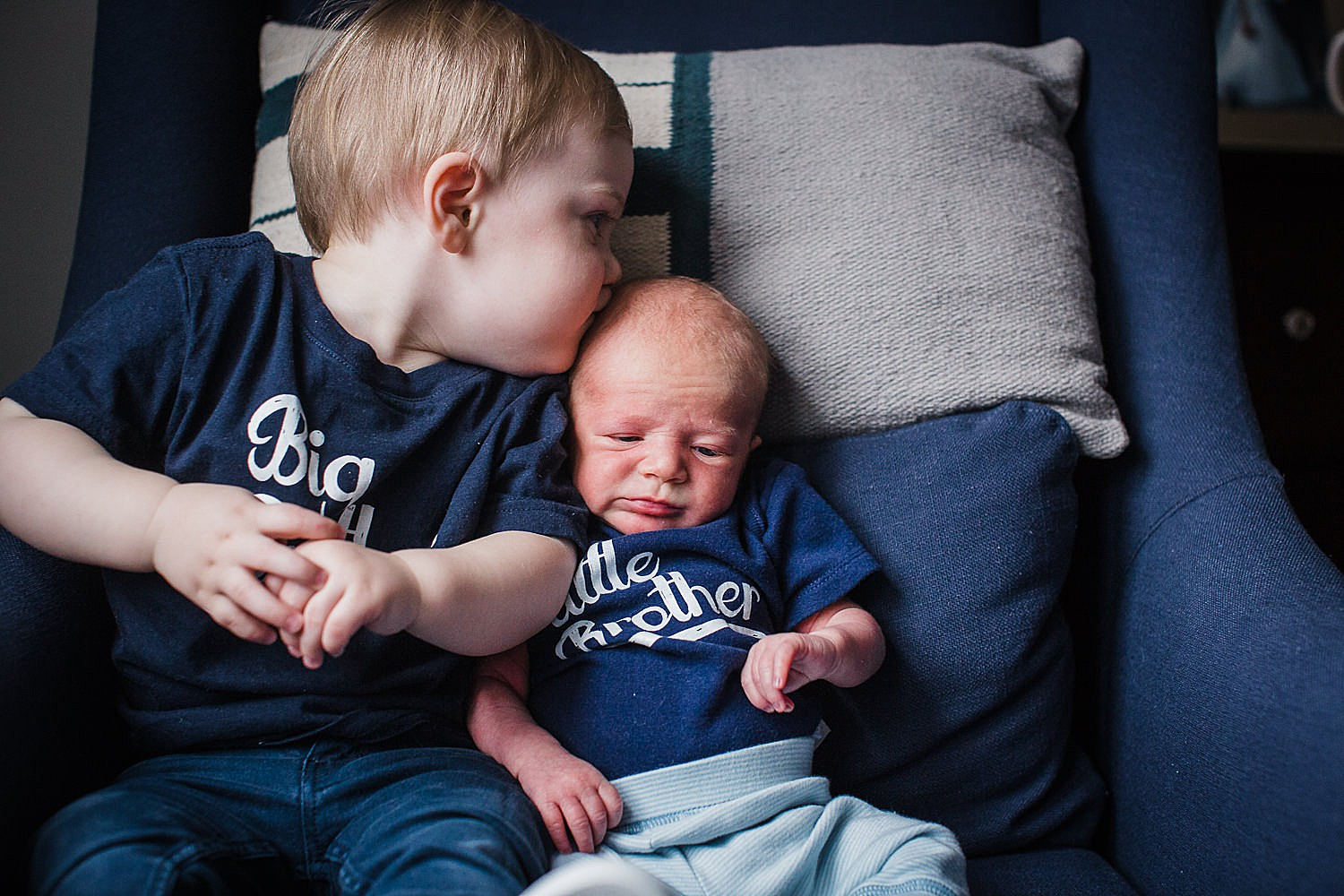 Photo of a toddler boy sitting in a blue sofa chair kissing his newborn baby brother.