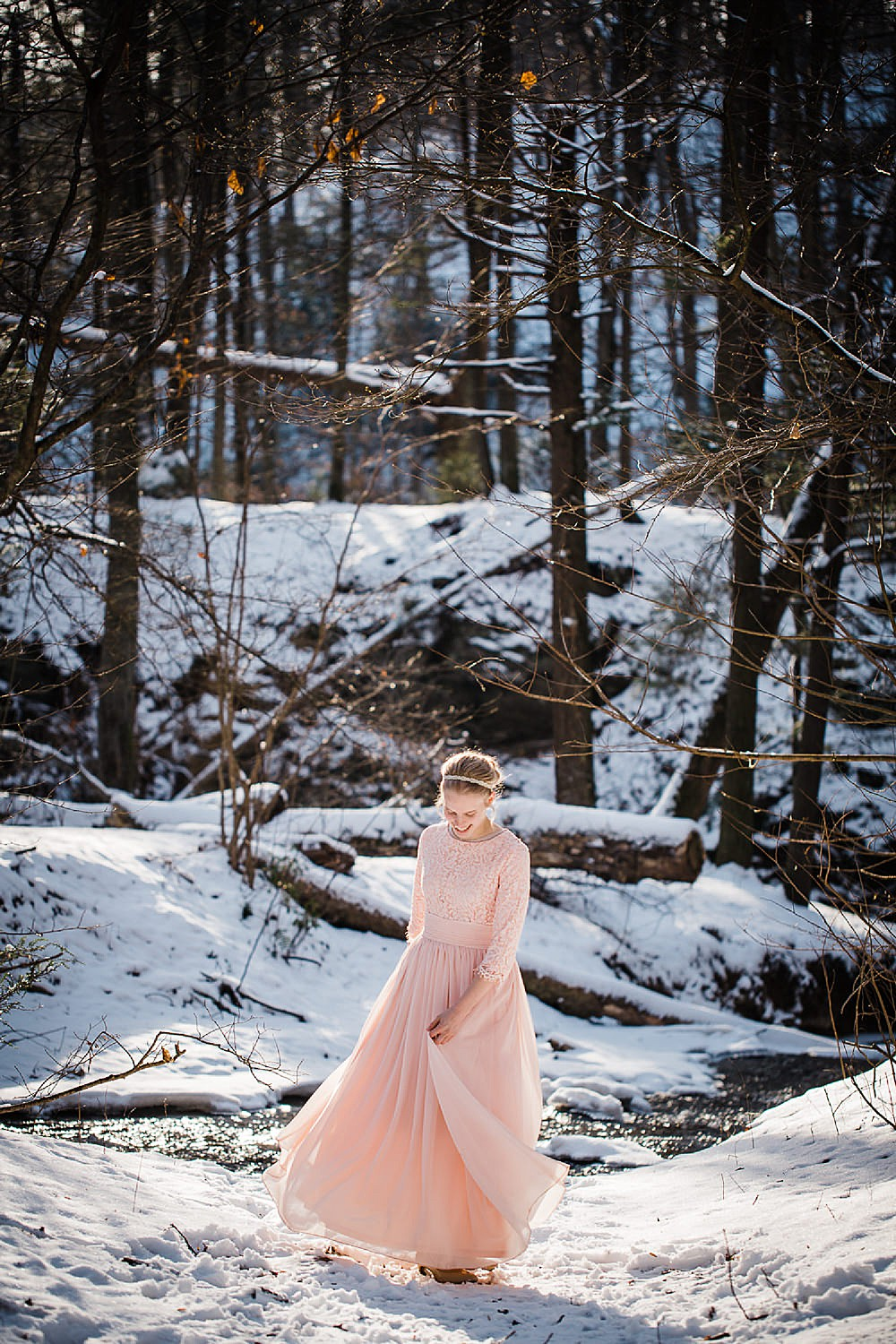 Photo of a young blonde woman in a long light pink gown twirling in a wintery forest.