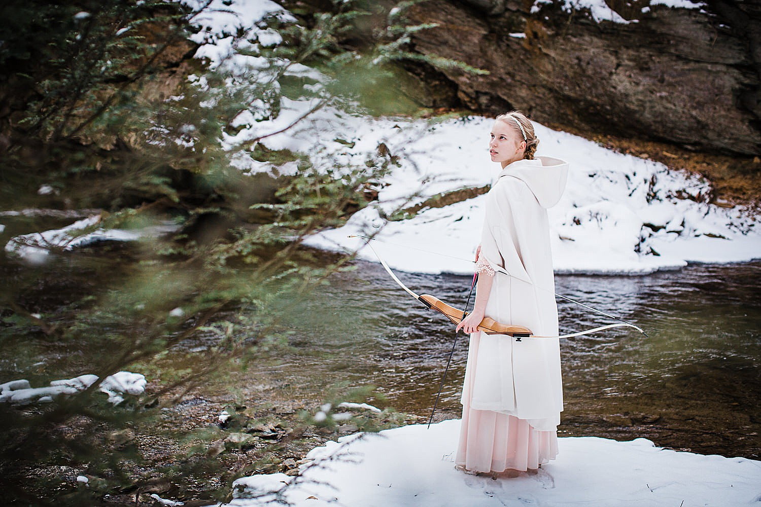 Photo of a young blonde woman in a long light pink gown and white hooded cape standing in a wintery forest with a bow and arrow.