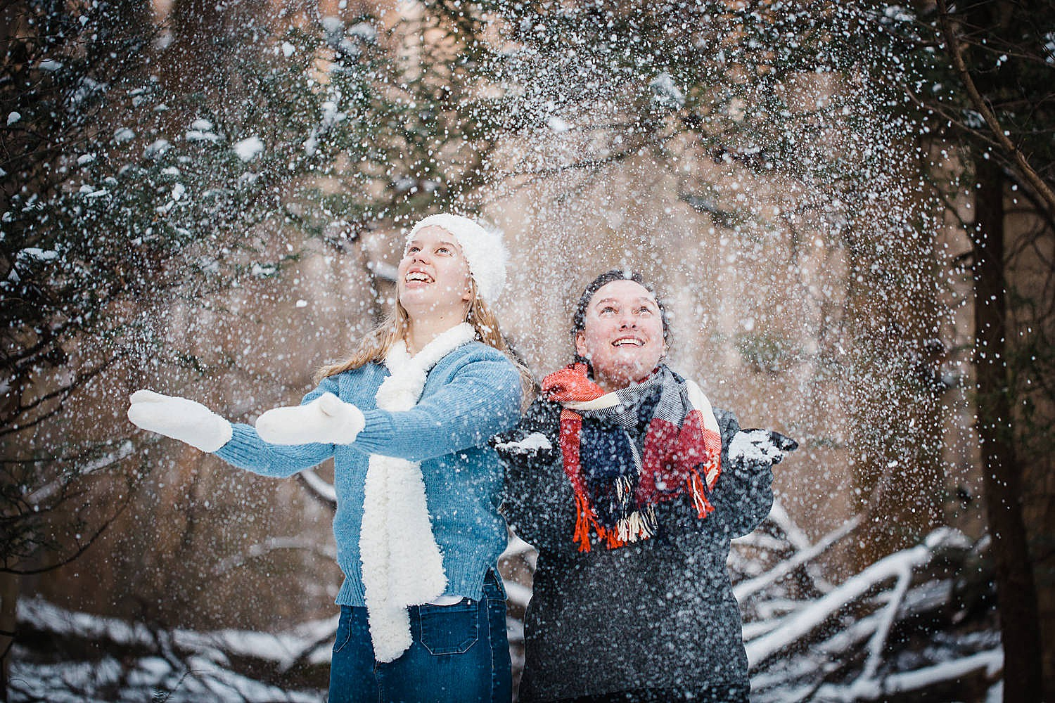 Photo of two young women throwing snow in the air in a wintery forest.