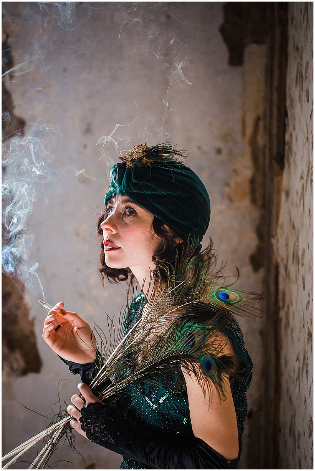 Photo of a glamorous young brunette woman wearing a green vintage flapper dress and a green velvet turban and peacock feathers holding a smoking cigarette in her hand.
