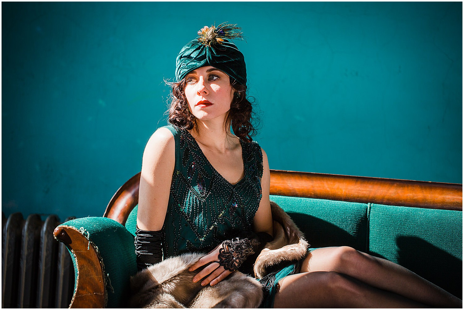 Photo of a glamorous young brunette woman wearing a green vintage flapper dress and a green velvet turban and peacock feathers.