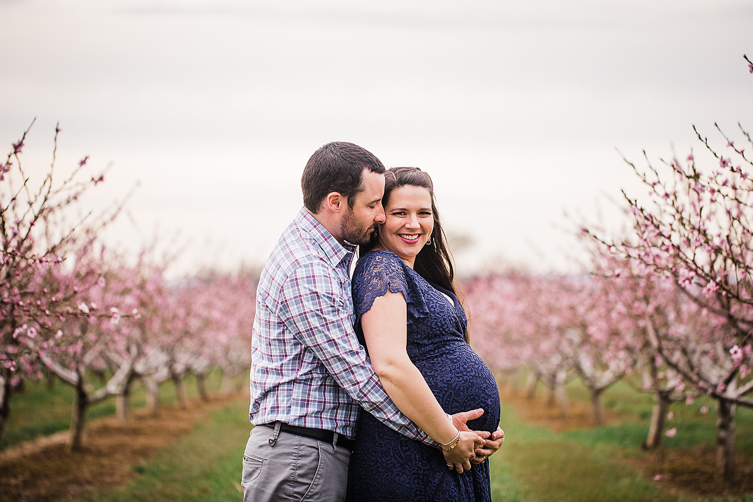 Photo of a pregnant woman in a blue lace dress standing with her husband in an orchard of flowers.