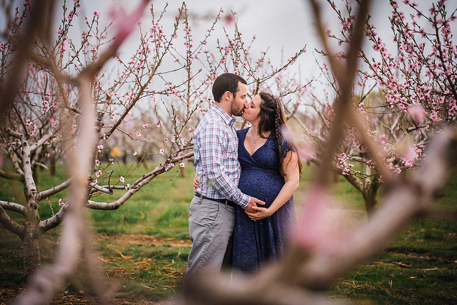 Photo of a pregnant woman in a blue lace dress kissing her husband in an orchard of flowers.