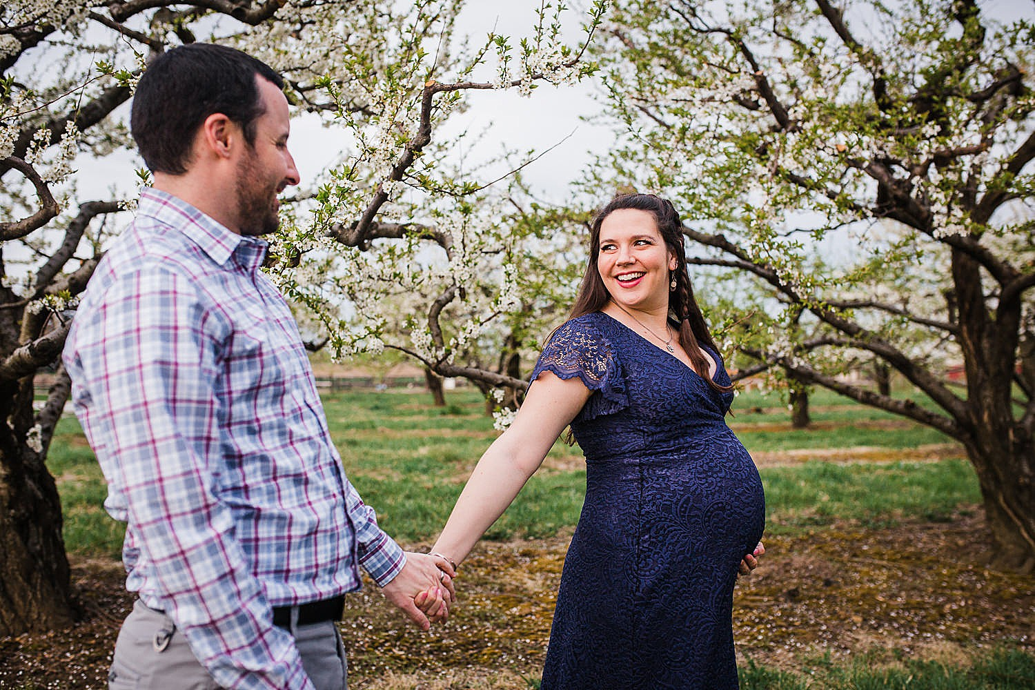 Photo of a pregnant woman in a blue lace dress walking with her husband in an orchard of flowers.