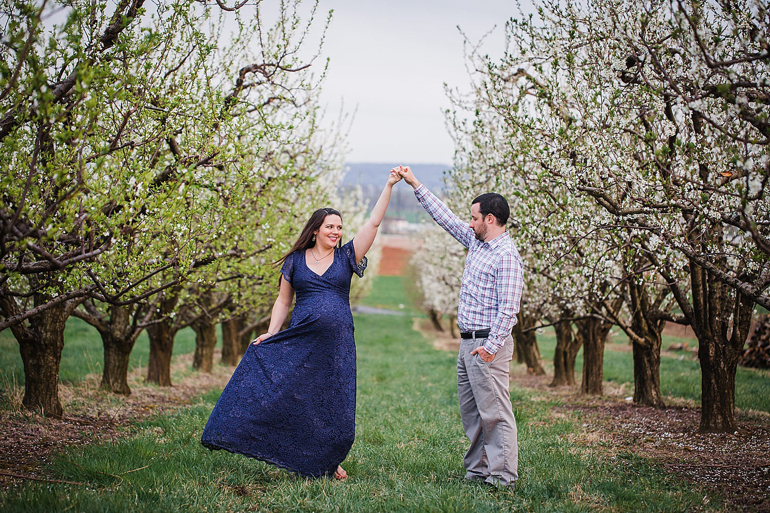 Photo of a pregnant woman in a blue lace dress dancing with her husband in an orchard of flowers.