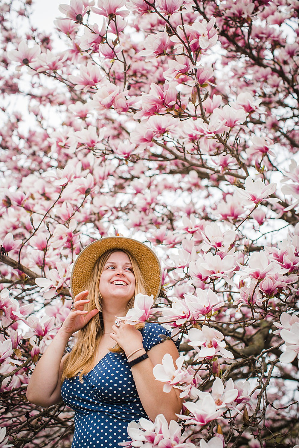 Photo of a young woman in a straw hat and polka dot dress standing in a tree of magnolia blossoms.