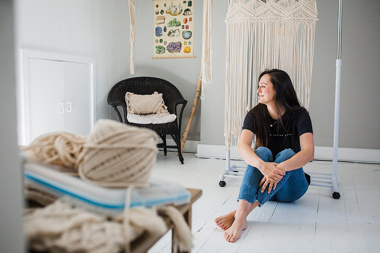 Photo of a young woman sitting in a bright studio space creating macrame art.